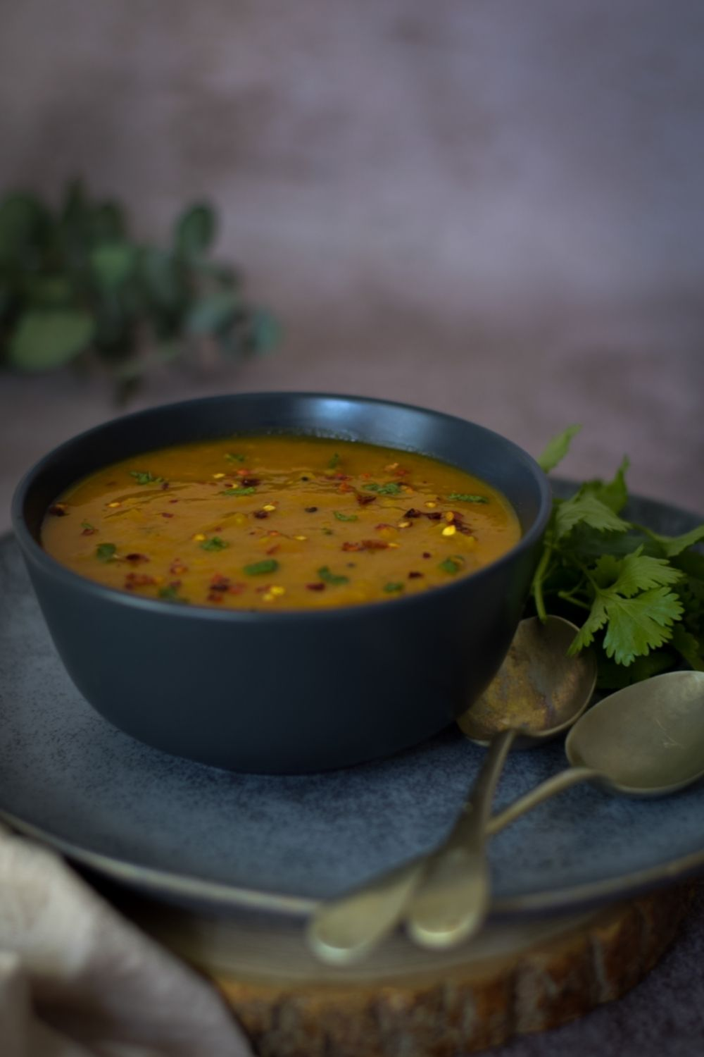 Masala Dal in a black bowl with spoons on the right side