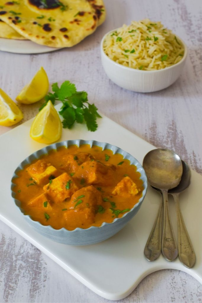 Butter Paneer in a blue bowl with spoons on right, lemons back left, rice and naan bread at the back