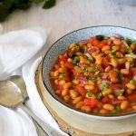 Baked Bean salad in a blue bowl on a piece of wood with spoons on left