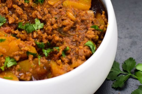 Mince curry with potatoes in a white bowl