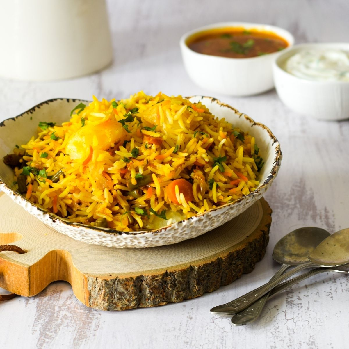 Vegetable biryani in a white bowl on a piece of wood with dal and raita at the back with spoons on right