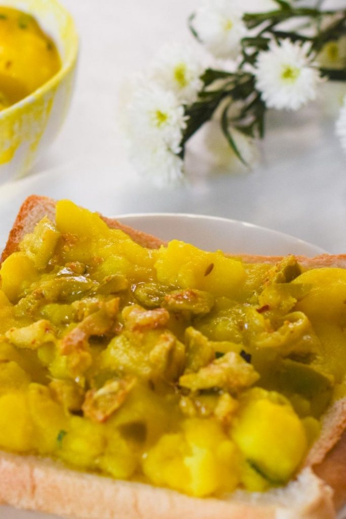 Potato Curry on a slice of white bread with flowers on the right and a bowl on the left