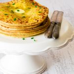 Roti stuffed with dal filling on a cake stand with 2 knives on the right