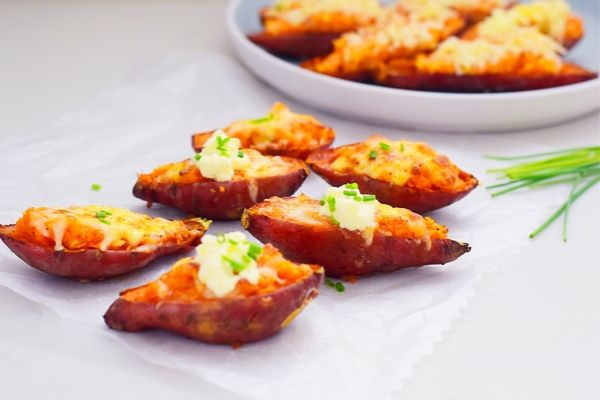 Loaded sweet potato on parchment paper and some on a plate