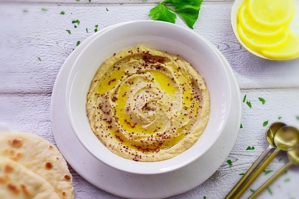 Creamy Homemade Hummus in a white bowl with pita bread and lemon on the side