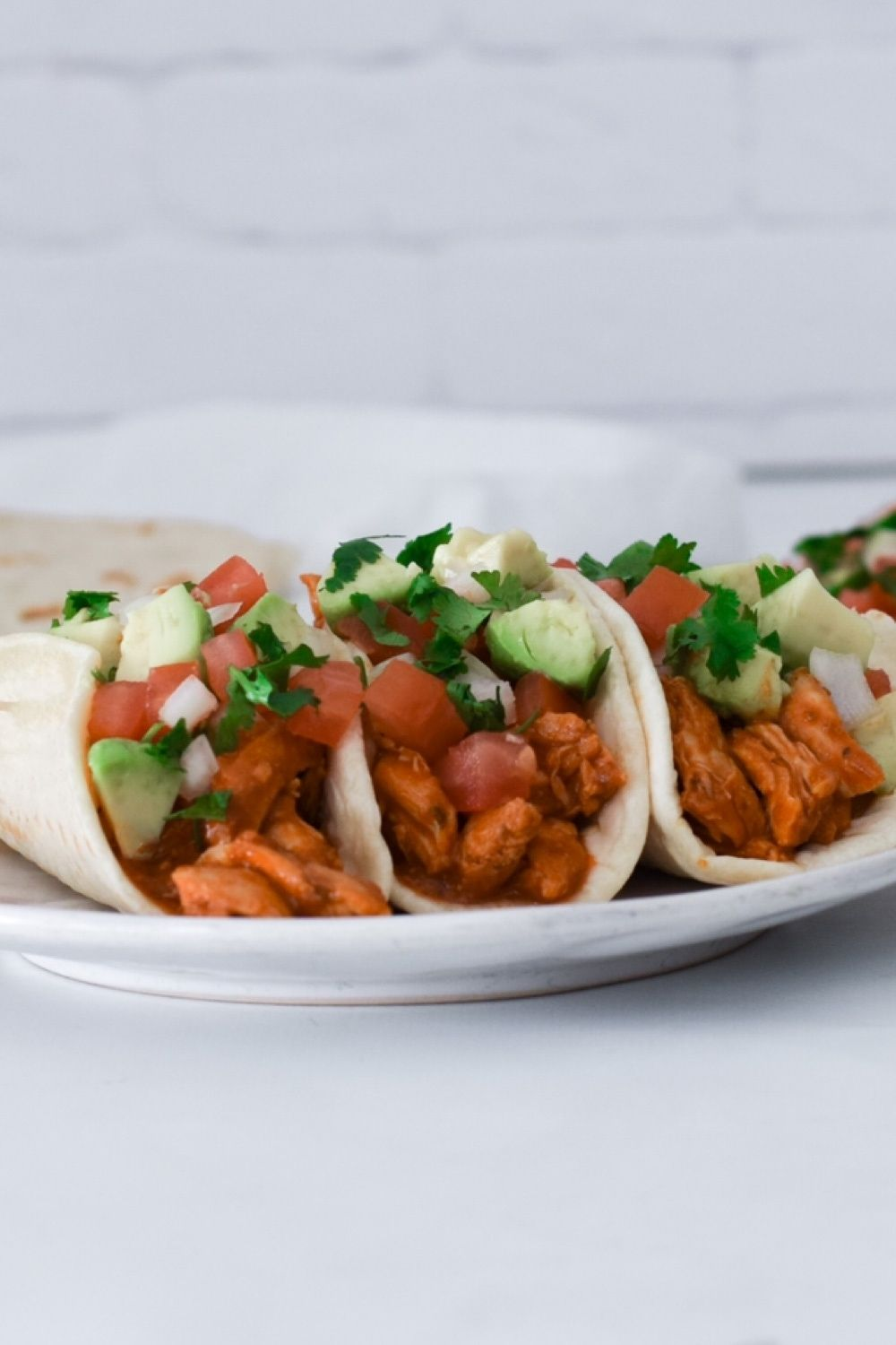 saucy chicken tacos in a white plate