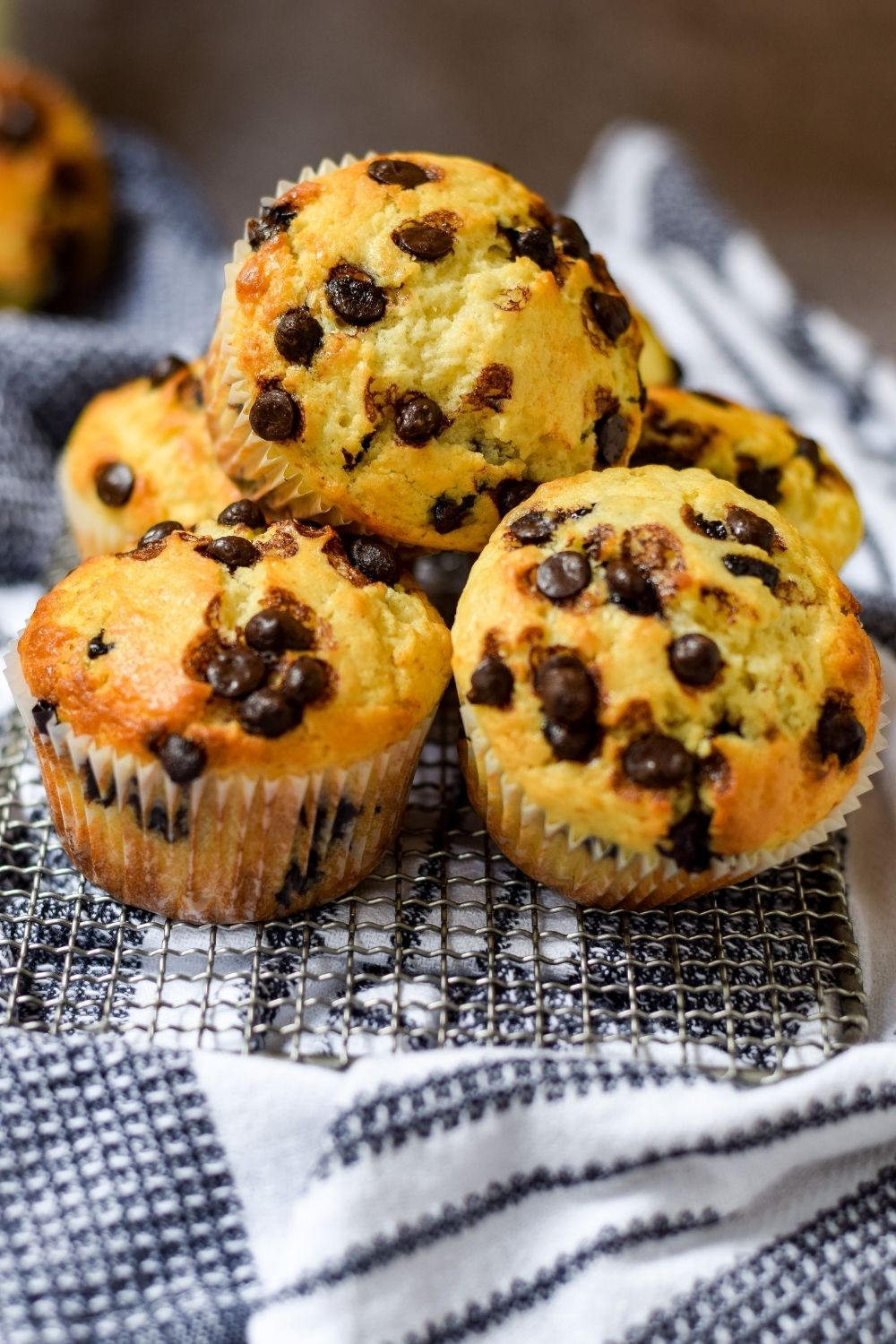 Vanilla Choc-Chip Muffins on a wire rack on top of a kitchen towel