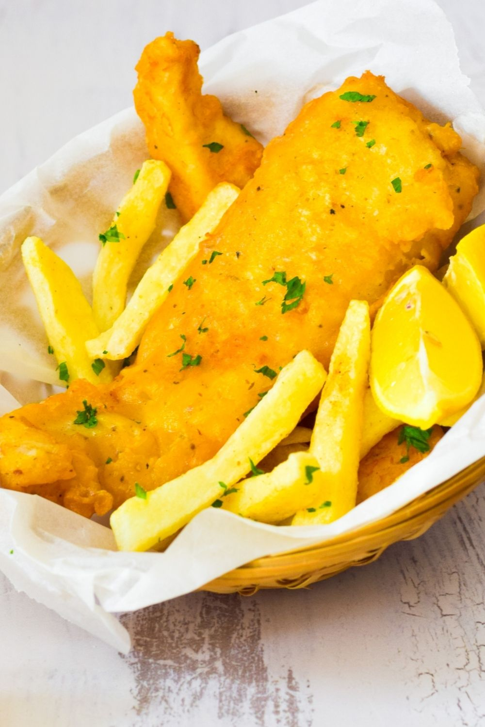 Crispy Battered Fish in a basket with chips and lemon