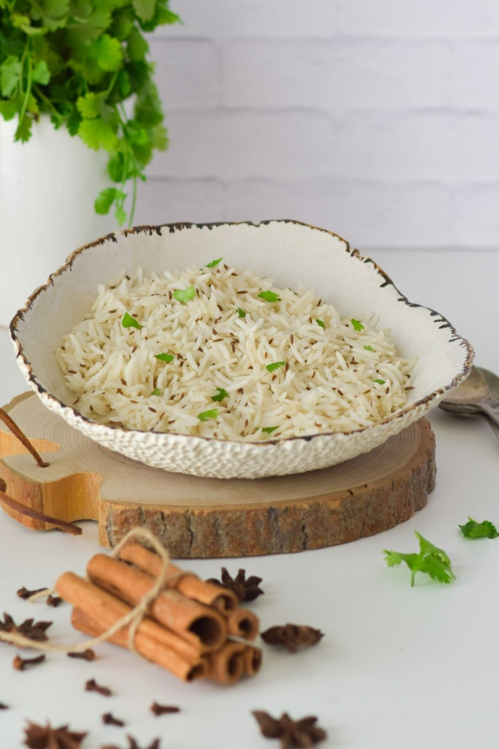Cumin Rice in a white bowl on a wooden board, coriander left back and spices in front