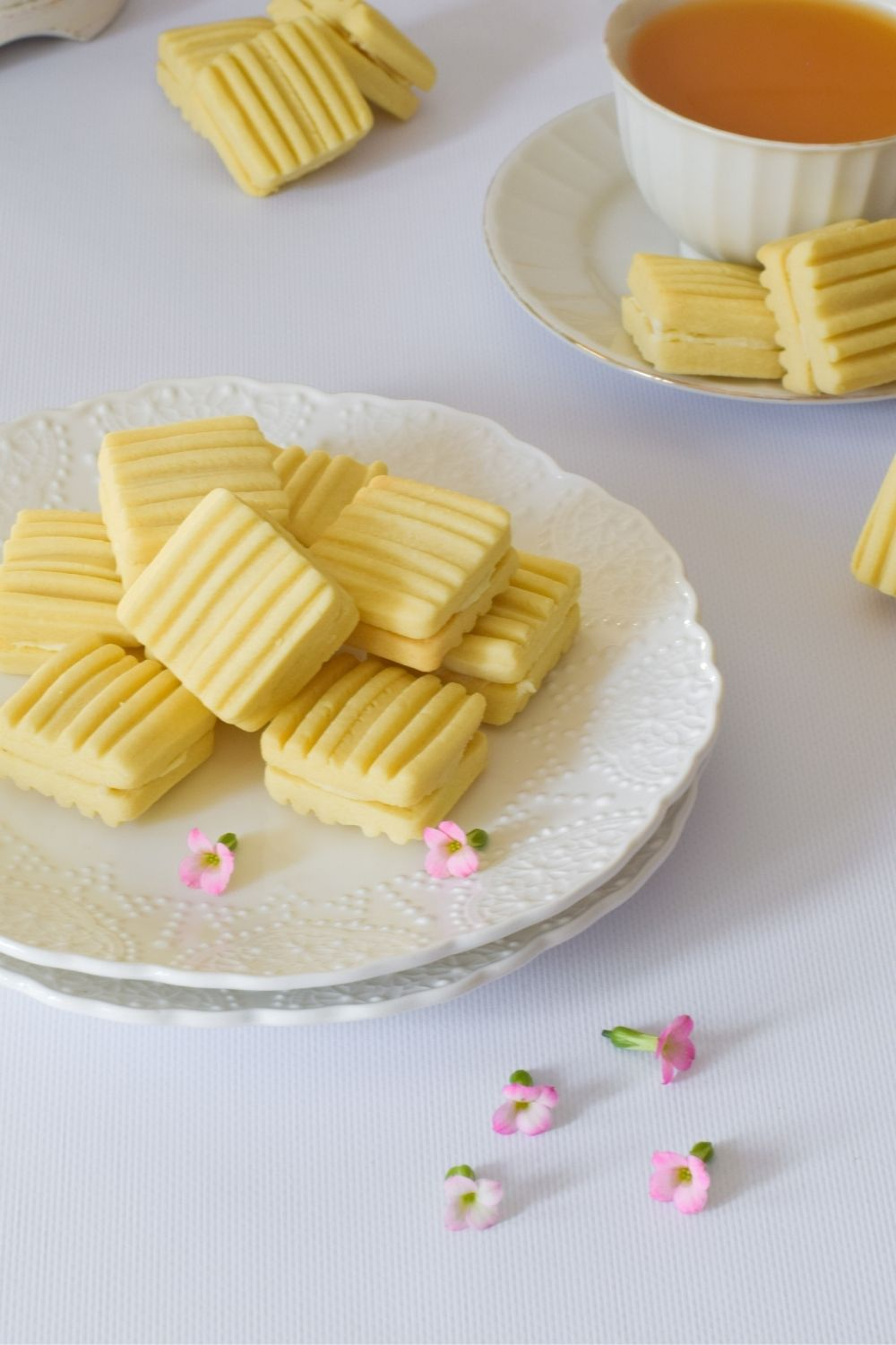 Royal Cream Biscuits on a white plate with tea on right and flowers in front