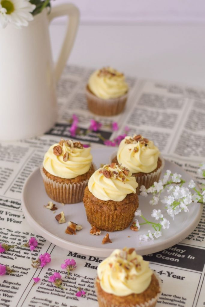 Carrot Cupcales on a white plate with pink flowers around and a vase back left