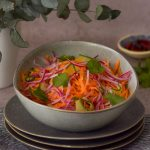 Carrot salad in a bowl with chilli at the back right and green leaves on the left