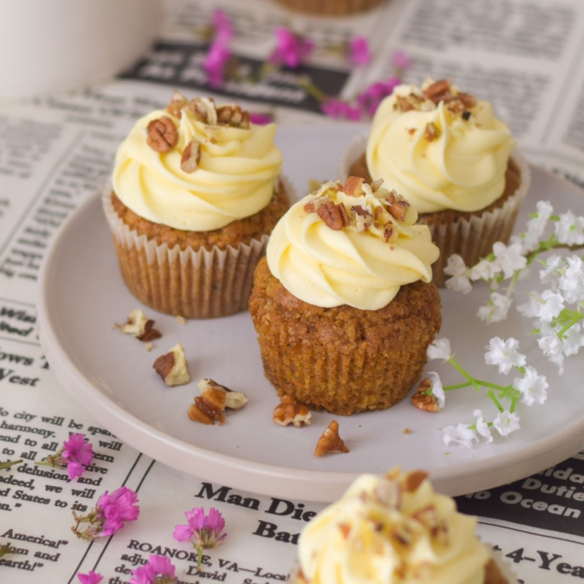 Carrot cupcakes on a white plate with white and pink flowers around