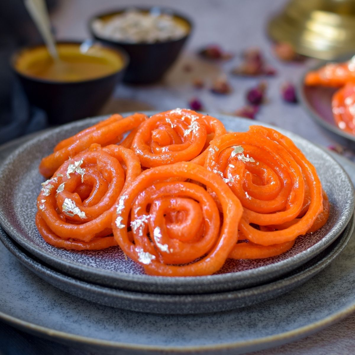 Jalebi in on stacked grey plates with cardamom and syrup back left and more jalebi on right