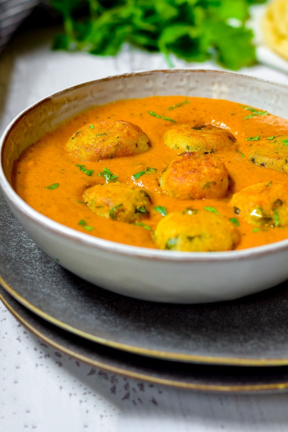 Malai Kofta in a white bowl on top of black plates with coriander at the back