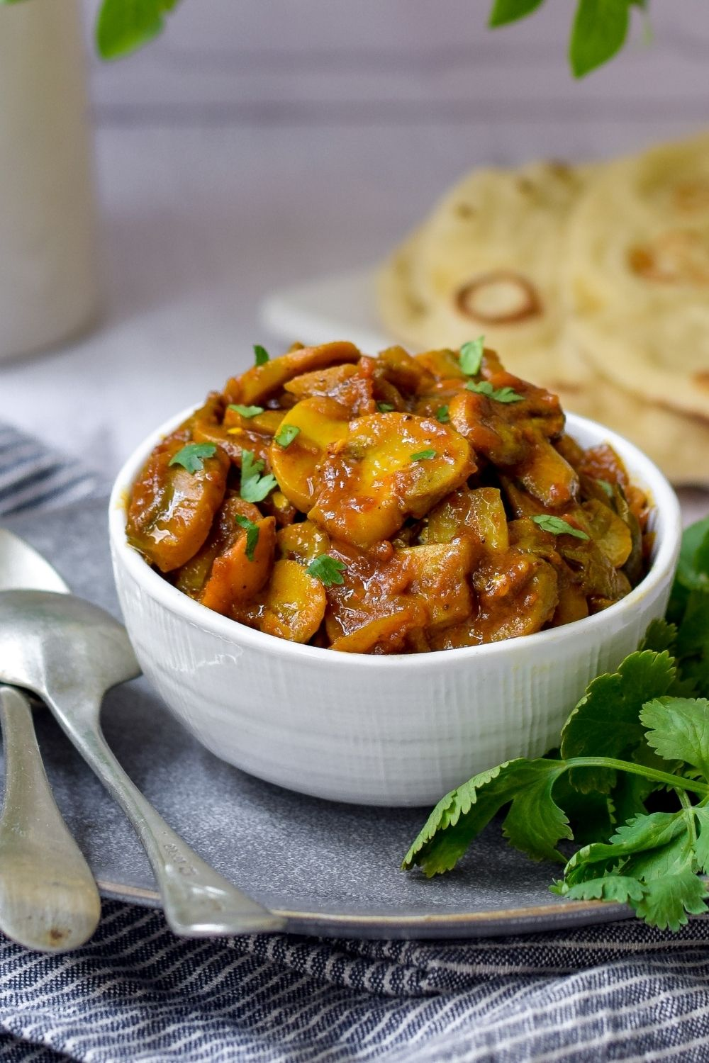 Mushroom Curry in a white bowl with naan bread back right and spoons on left