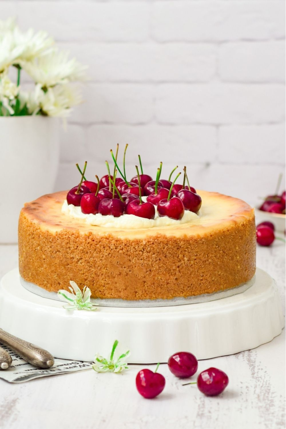 Baked white cheesecake decoarated with cherries on a white dish