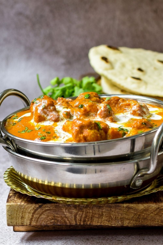 Cauliflower Tikka Masala in a silver bowl with naan bread i