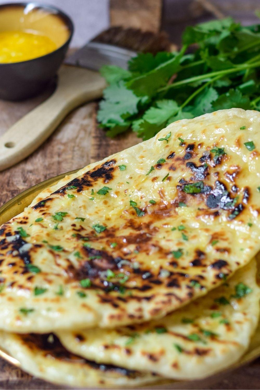 Cheesy Garlic Naan Bread on a wooden board