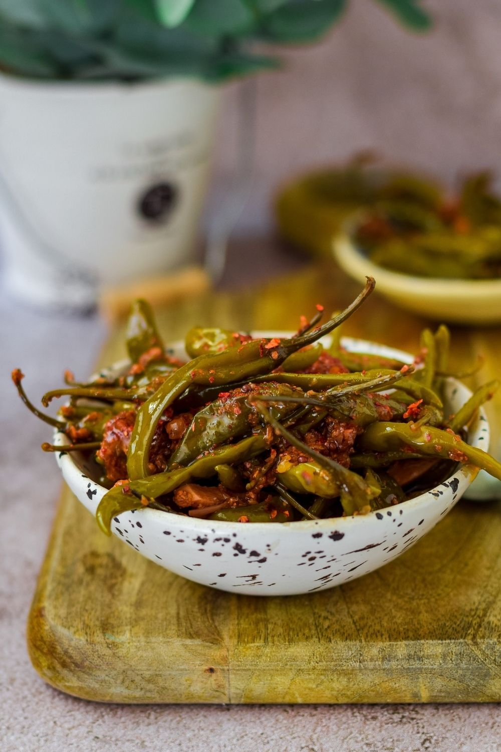 Pickled chillies in a white speckled bowl on a wooden board